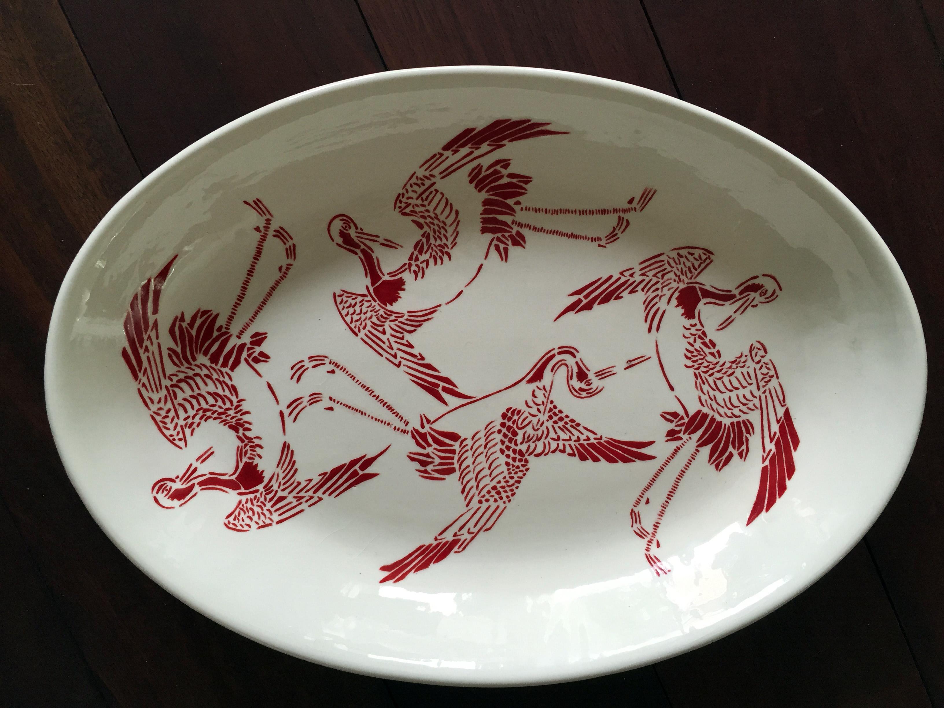 Binnenkant ovale schaal met kraanvogels en egaal rode onderkant